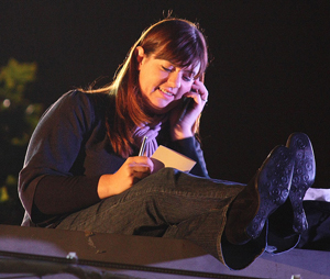 A young woman texting a friend at night.