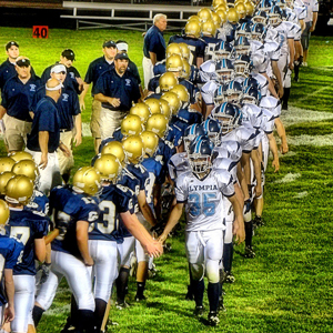 photo of two high school football teams shaking hands after a game