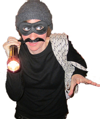 A woman dressed in a humorous burglar costume at a party. She is wearing a silly stick-on moustache and mask, and looks like she's creeping around the kitchen with a flashlight.