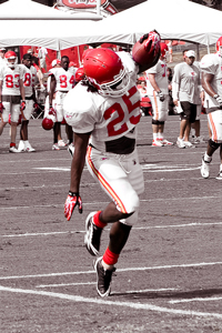 A football player at practice. The image is black and white except for the red of the player's uniforms. The camera has caught a player balancing on one foot, almost like he's hanging in the air.