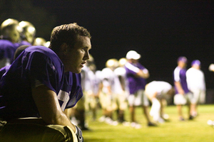 A player resting after a scrimmage in a football game. The image is somber and dark, except for the player's purple jersey.