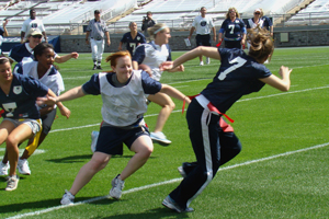 photo of young women playing flag football on a football field. Coaches and an umpire looks on in the background.