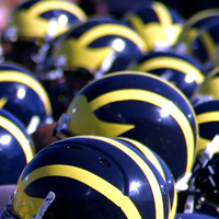 A crowd of blue and gold football helmets