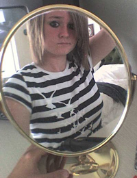 A photograph of a teenage girl looking at herself in the mirror.