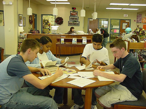 A photograph of students sitting around a table in a library studying