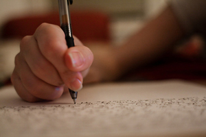 A photograph of a person's hand using a pen to write on a piece of paper