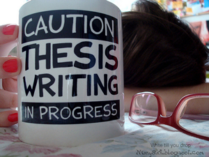 """photo of a writer with head on a desk and coffee mug and reading glasses in the foreground. The mug reads """"Caution Thesis Writing in Progress."""""""
