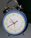 A photograph of an old-fashioned wind up alarm clock with bells on top of it