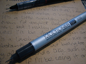 = A photograph of two fine point pens laying on a piece of paper with handwriting on it