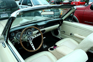 A photograph of the interior of a 1968 convertible Ford Mustang with the top down