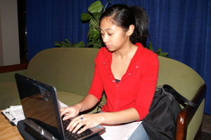 A photograph of a female student working on a laptop computer