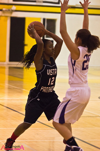 A photograph of two female high school basketball players on the court during a game