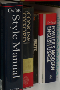 A photograph of writing resource books; a style manual, a dictionary, a thesaurus, and a book on modern English usage.