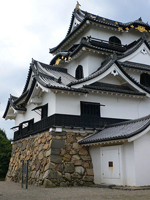 A photograph of the Hikone castle in Japan. It has several layers of swept gables typical of classic Japanese architecture.