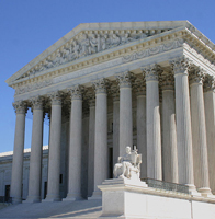 A photograph of the United States Supreme Court courthouse. It is a White marble building that was designed to look Greco Roman in that it has large columns and an elaborately decorated façade.