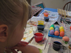 Photograph of a child dyeing Easter eggs