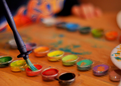 Photograph of a palate of watercolors and paints with a brush