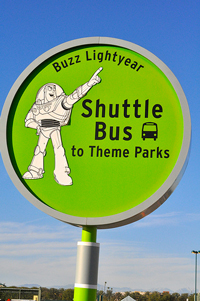 A photograph of a sign that indicates that the shuttle bus to theme parks stops here. There is picture of Buzz Lightyear from Toy Story on the sign.