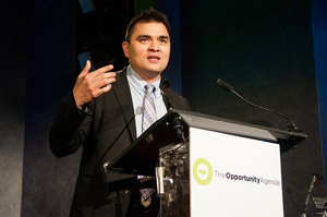 A photograph of Jose Antonio Vargas giving a speech. He is wearing business attire, and standing behind a podium.