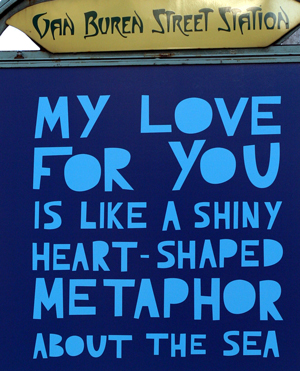 "A sign from Van Buren Street Station in Chicago. The sign reads ""My love for you is like a shiny heart-shaped metaphor for the sea."""