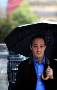 Author David Sedaris walking under an umbrella in the rain