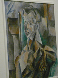 Pablo Picasso painting: a cubist rendition of a woman in browns and greens.