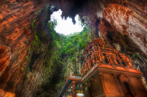 A photograph from below of a decorated, painted temple, a tall building covered in statues and decorations. It seems dwarfed by the what might be the mouth of a cave or extinct volcano overhead, a tunnel leading into sunlight, draped with vines and trees.