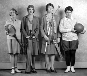 Four college aged women dressed in 1920's gym clothing and holding various sporting equipment.