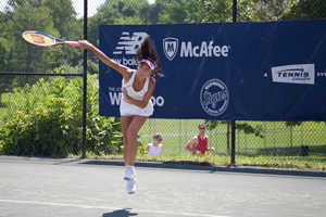 A woman's tennis game. The photograph shows a player appearing to hang in the air as she jumps to return a shot. A banner behind her advertises several local businesses and a few software companies.