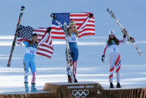 The gold medal award in women's downhill skiing from the 2010 Vancouver Olympics. Three athletes stand on the pedestal, holding their skis over their heads in triumph.