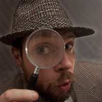A bearded dressed as Sherlock Holmes peers through a magnifying glass at the camera.