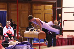 photo of a male gymnast practicing a routine on a pommel horse