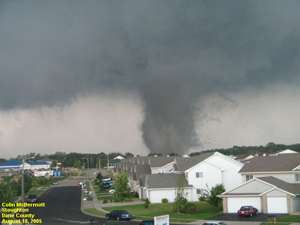 A photograph of a tornado touching down at the edge of a housing development