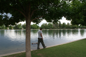 photo of a young man walking on the edge of park lake