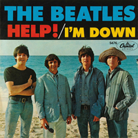 A photograph of The Beatles record sleeve HELP! And I'm Down. It shows the four members of the group standing on a beach.