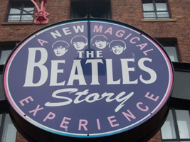 A photograph of a sign that reads: A New Magical Experience: The Beatles Story. It also features images of the Beatles faces.