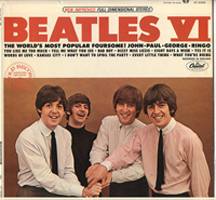 """A photograph of the Beatles record sleeve: """"Beatles VI."""" It has a photo of the band with their arms extended with their hands lain on top of each other."""