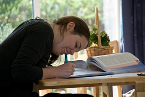 A photograph of a female student at a desk writing. She has a textbook open on her desk as well
