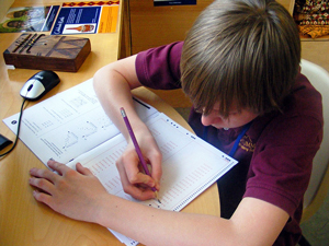 A photograph of a male student working on a test booklet