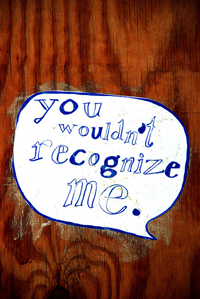 """A photograph of a sign on a door that reads """"You wouldn't recognize me."""""""