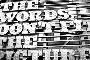 A photograph of a sign with part of the words outside of the frame. It reads: The words don't fit the picture.