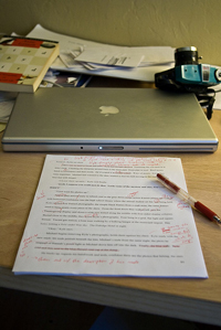 A photograph of a printed paper on a desk with a laptop, books, papers, and a camera. There is a pen laying on the printed paper, which has been marked by the pen.