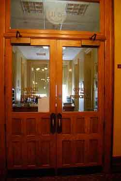 """Photo of two big wooden doors with large glass panes on which is written """"The Office of the Principal"""""""