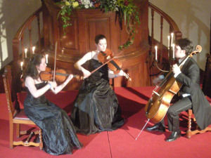 A photograph of a string trio consisting of two violins and a cello. The musicians, two women and a man, area all wearing formal attire.