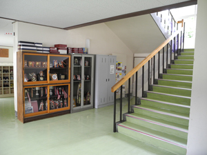 A photograph of a stairwell in a school. Next to the stairs is a trophy case and several lockers.