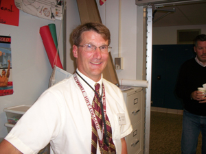 A photograph of a male teacher in a school. He is wearing glasses and has several lanyards hanging around his neck.