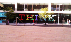 """A photograph of a large sign outside of a building lobby. The sign reads """"THINK""""."""