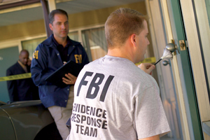 A photograph of two FBI officers at a crime scene. One of them has a t-shirt that indicates that he is an Evidence Response Team member.