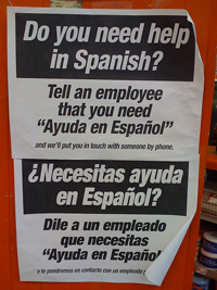 """A photograph of a sign that reads """"Do you need help in Spanish: Tell an employee that you need 'Ayuda en Espanol.'"""""""