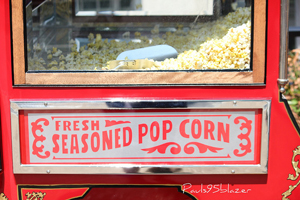 """A photograph of a large popcorn popper. It has a sign that reads """"Fresh Seasoned Popcorn"""""""